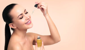 woman applying facial serum on pink background, bring out my beauty