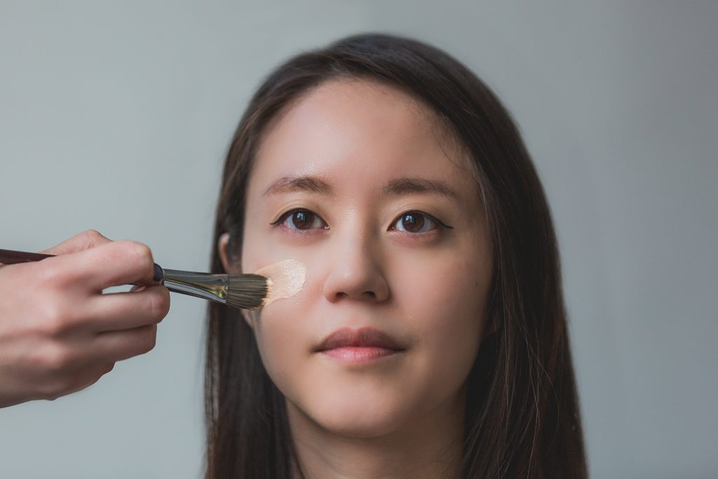 woman having foundation applied to her face