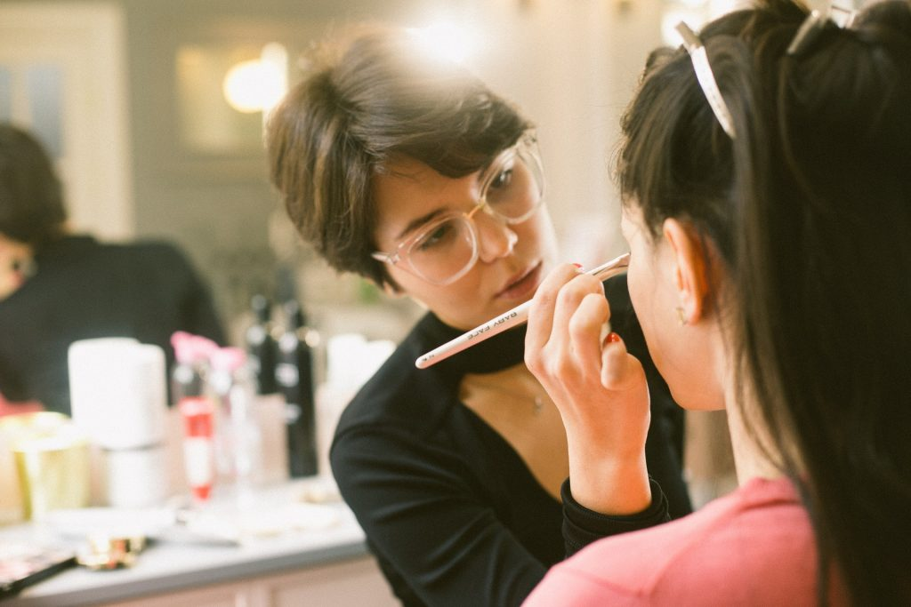 makeup artist working in studio on a woman's face