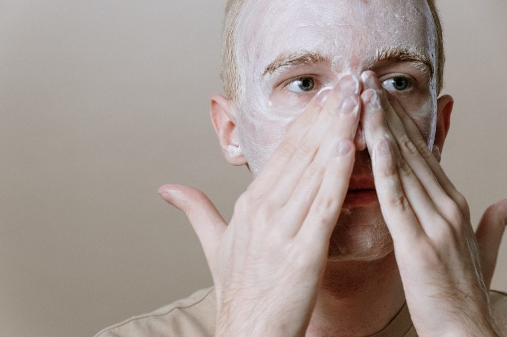 man washing face with soapy product