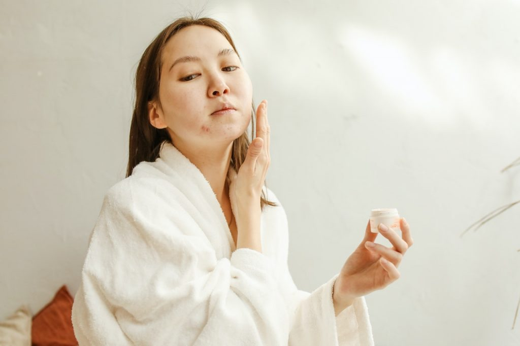 woman in a white robe applying acne product