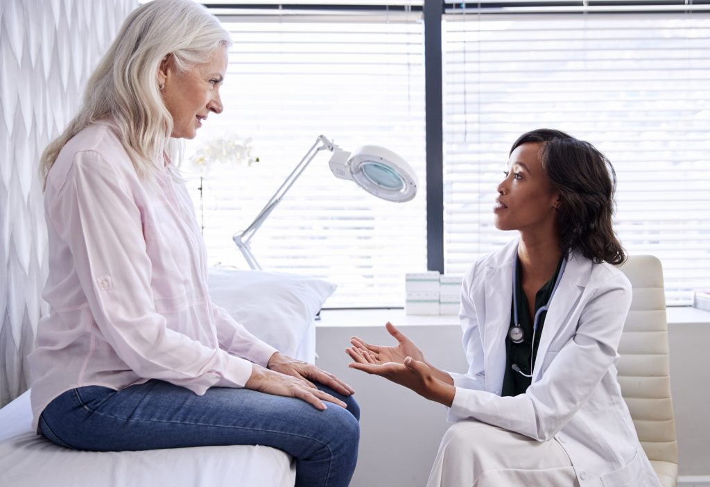 older woman talking with female physician