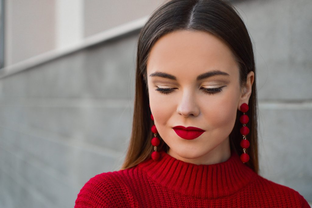 Woman with smoky eyes, a bold red lip, red earrings and red sweater dress