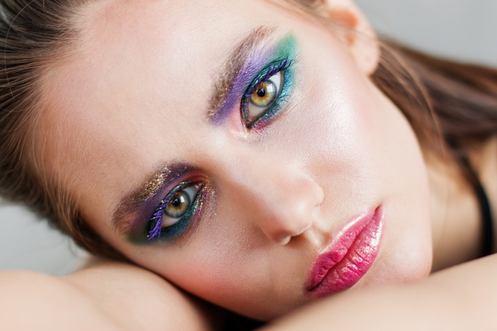 Beautiful women with bright vivid purple  and green eyeshadow. When choosing makeup for deep set eyes, looks for ones that are long lasting and don't smear.  Vegan and Cruelty Free options are also best.