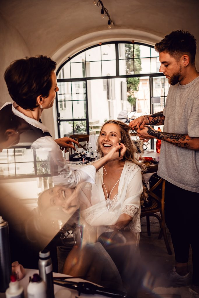 Makeup artist applying makeup to woman while hair stylist styles her hair.  Hazel eyes give you flexibility in your makeup colors and routine.  Try a simple everyday look or a dramatic evening look.