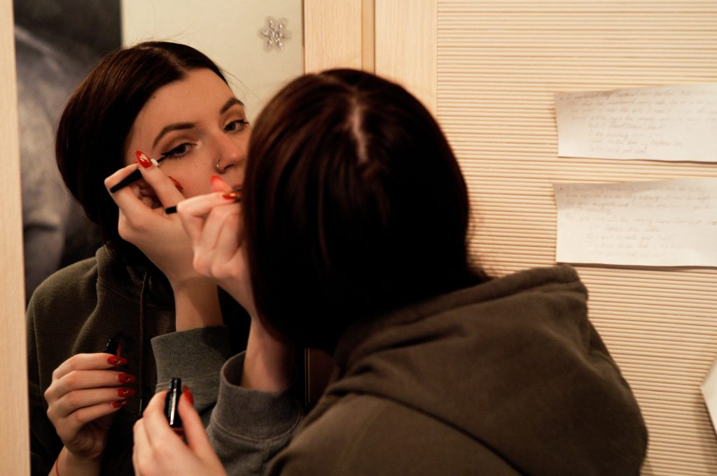 woman applying eyeliner and looking in the mirror.  With deep set eyes you don't want dark shades.  Use eyeliner in a thin, smoother line that follows the curve of your eye