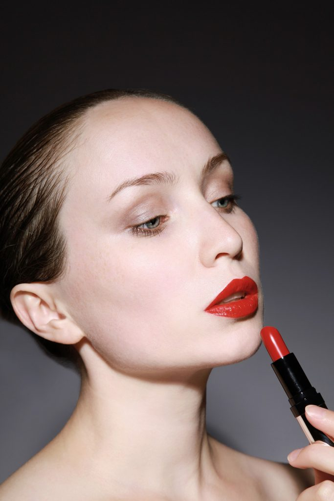 Fair skinned woman applying red lipstick that will complement a red dress