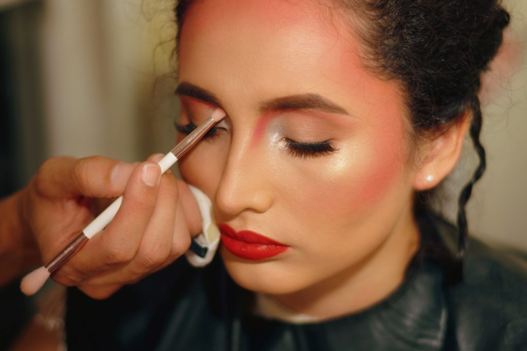 Makeup artist applying professional makeup on women. When choosing makeup for neutral undertones, looks for products that are easy to apply and blendable.