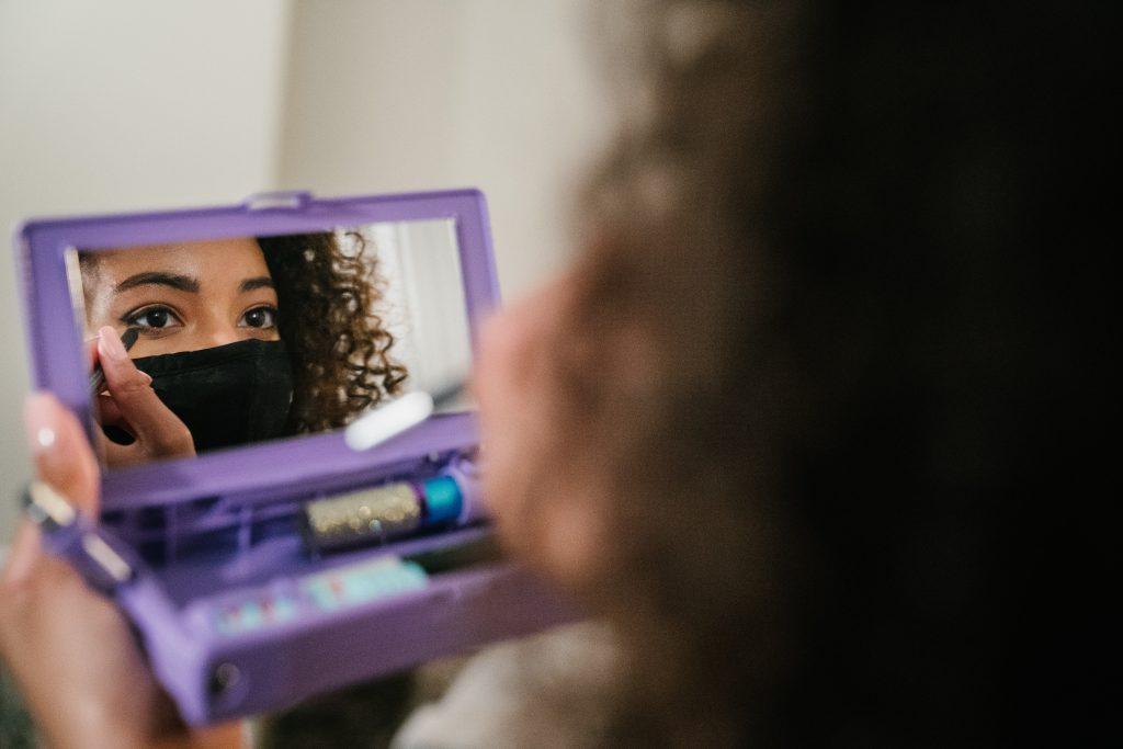 Woman putting makeup on eyes in front of mirror. The first step in choosing the best makeup for neutral undertones is to avoid makeup designed for people with warm or cool tones.