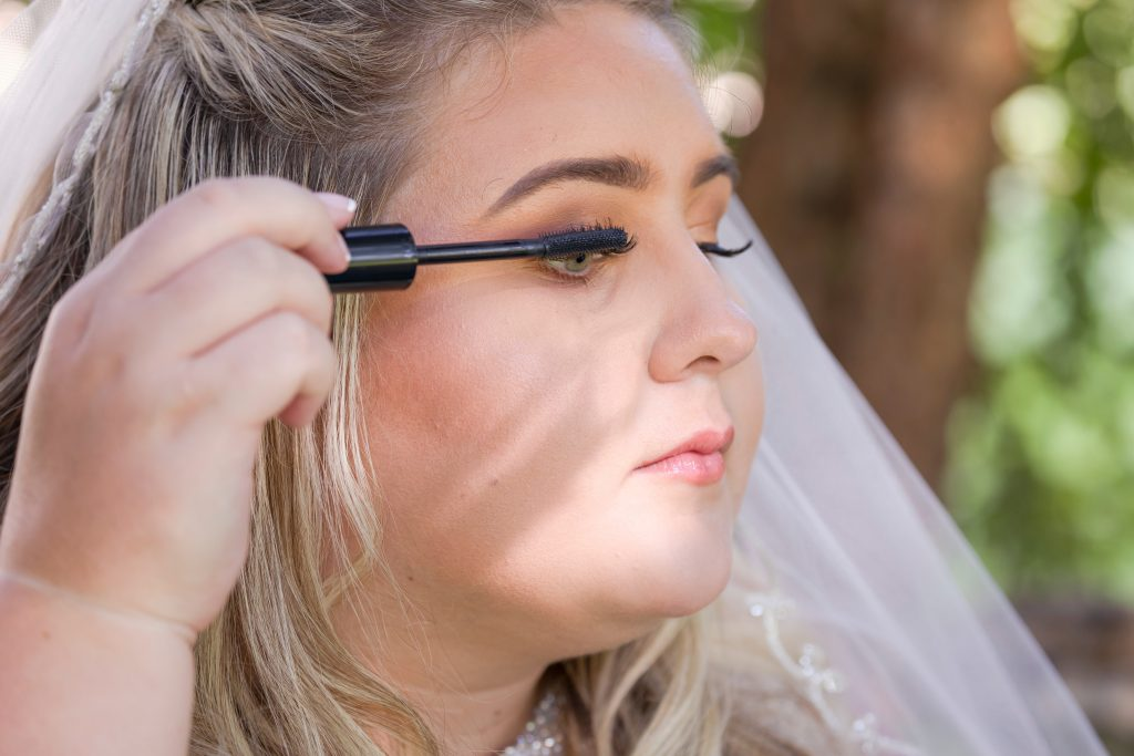 Beautiful bride applying mascara on eyes.  The best makeup for deep set eyes is makeup that brightens your eyes and makes them stand out.