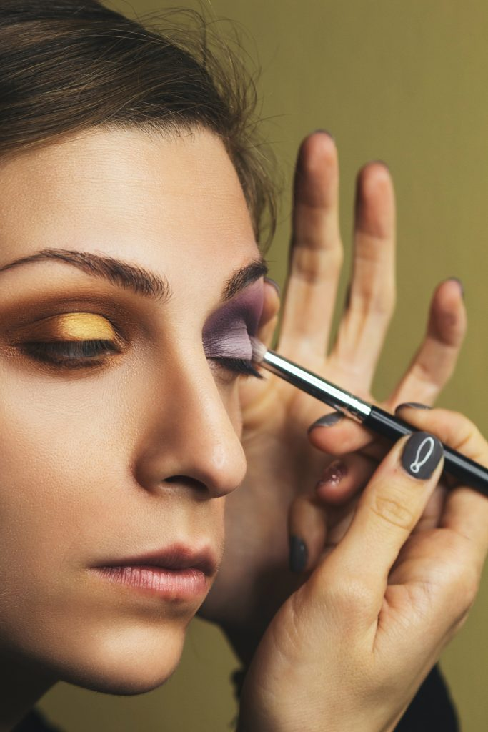 Woman applying gold and purple eyeshadow. Since gold is one of the prominent tones in hazel eyes, gold eye shadow is a good color choice