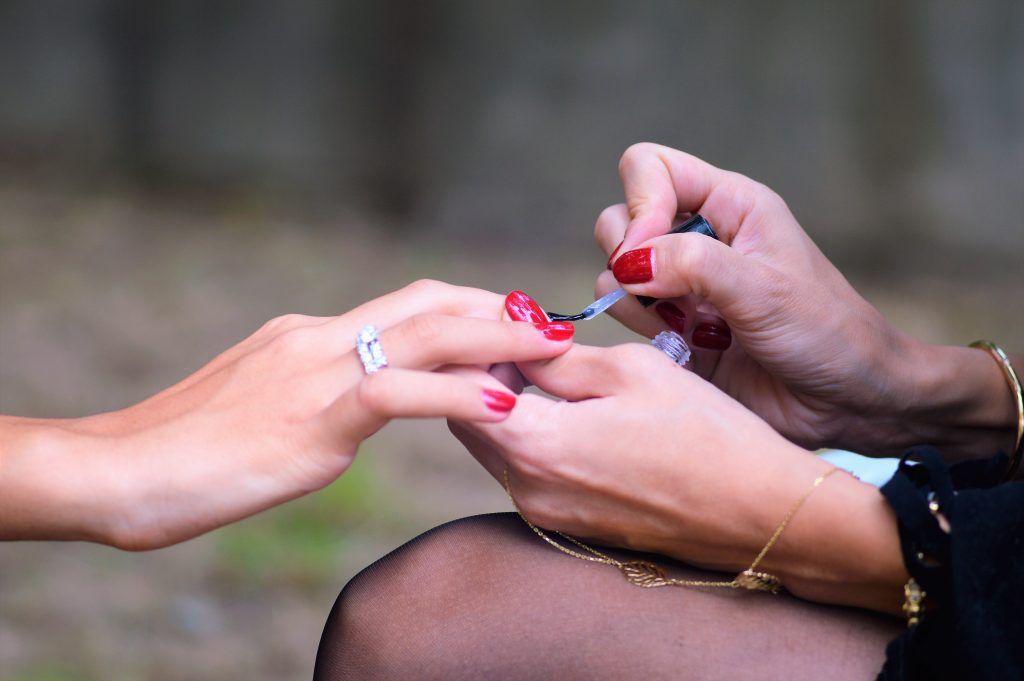 woman painting another woman's nails with red nail polish