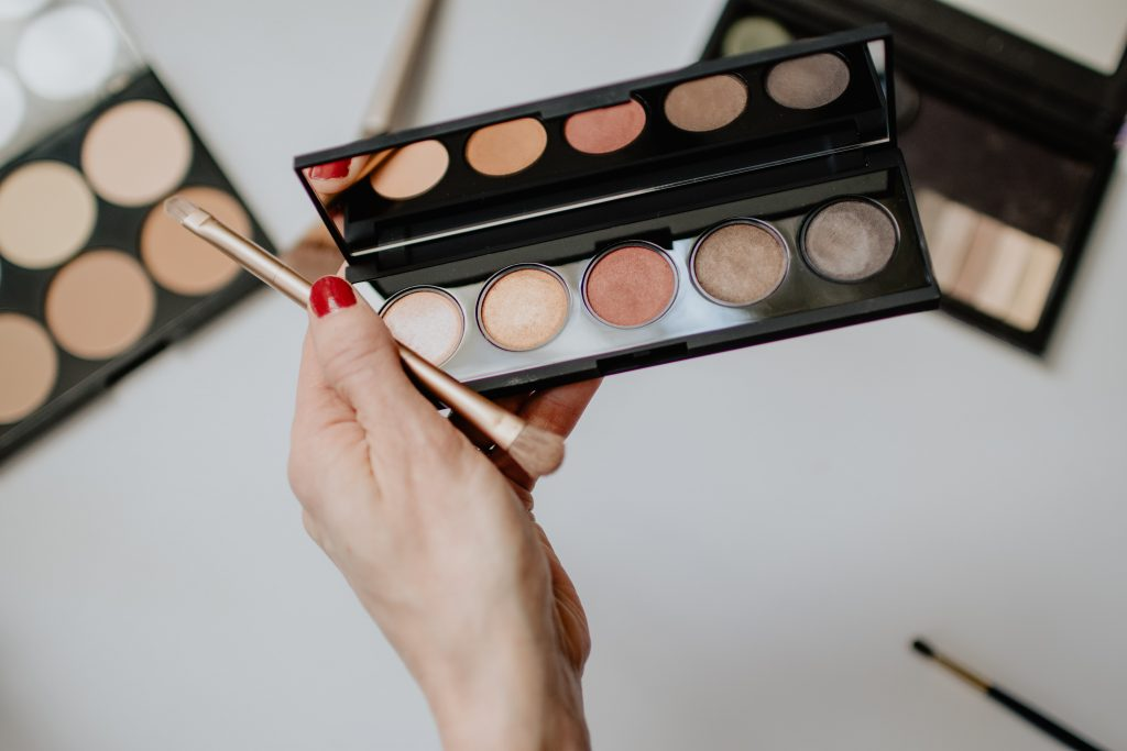 woman holding Beautiful eyeshadow palette and brush.  Choose neutral and nude shades if you are a neutral beauty.