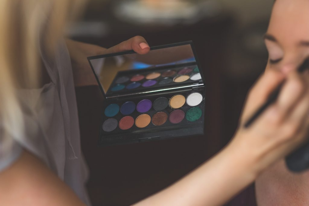 Makeup artist holding palette and brush while applying to client.  Look for makeup that is easy to apply, long lasting, and blendable.