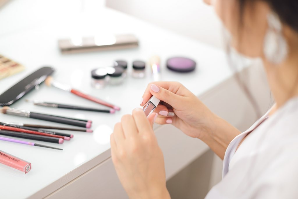 Woman sitting in front of makeup collection. The best Makeup for red dress can be subtle or bold