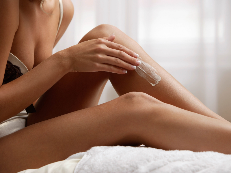Woman Applying Lotion to Legs.  Self Tanning Lotions Build Your Tan Gradually