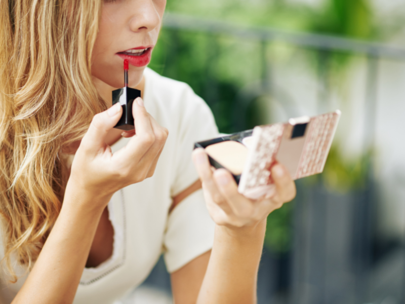 Blong woman applying liquid lipstick.   We let you know which are the best Non Drying Liquid Lipsticks