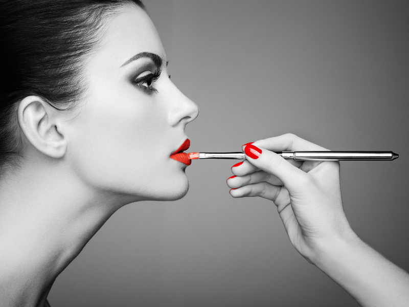 Best Liquid Lipstick Brands.  Makeup artist putting liquid lipstick on model in profile.  Artsy, black and white and red photo