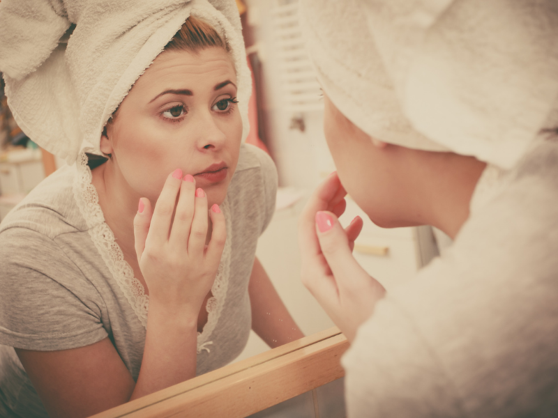 Woman Looking in Mirror. We imagine that she is asking: What is the best makeup for Large Pores and Wrinkles?