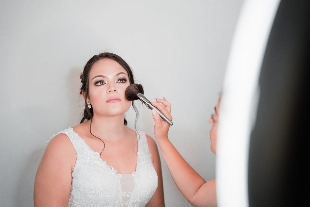 bride having makeup applied by brush in front of lighted mirror.  If you have neutral undertones, opt for peach and other neutral shades