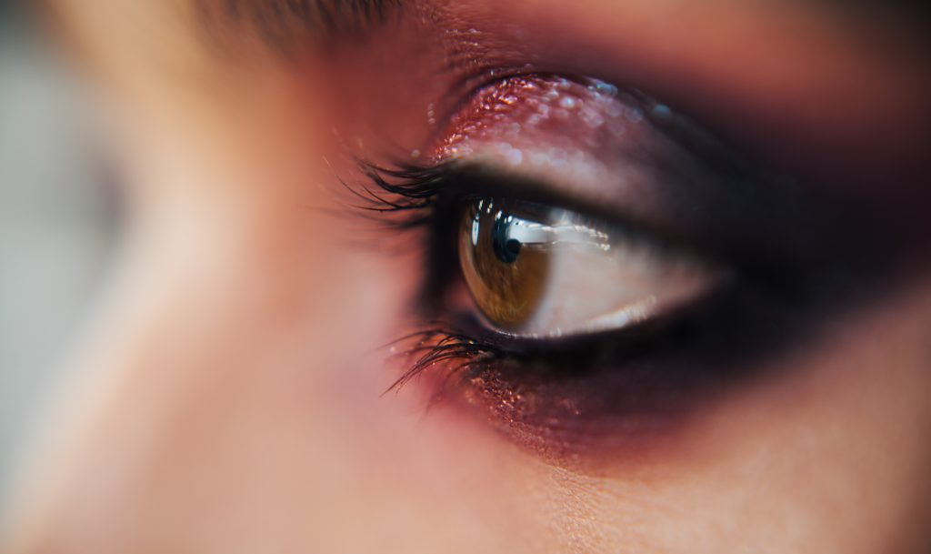 close up of hazel eye with purple eyeshadow.  Purple is an excellent makeup color for haze eyes
