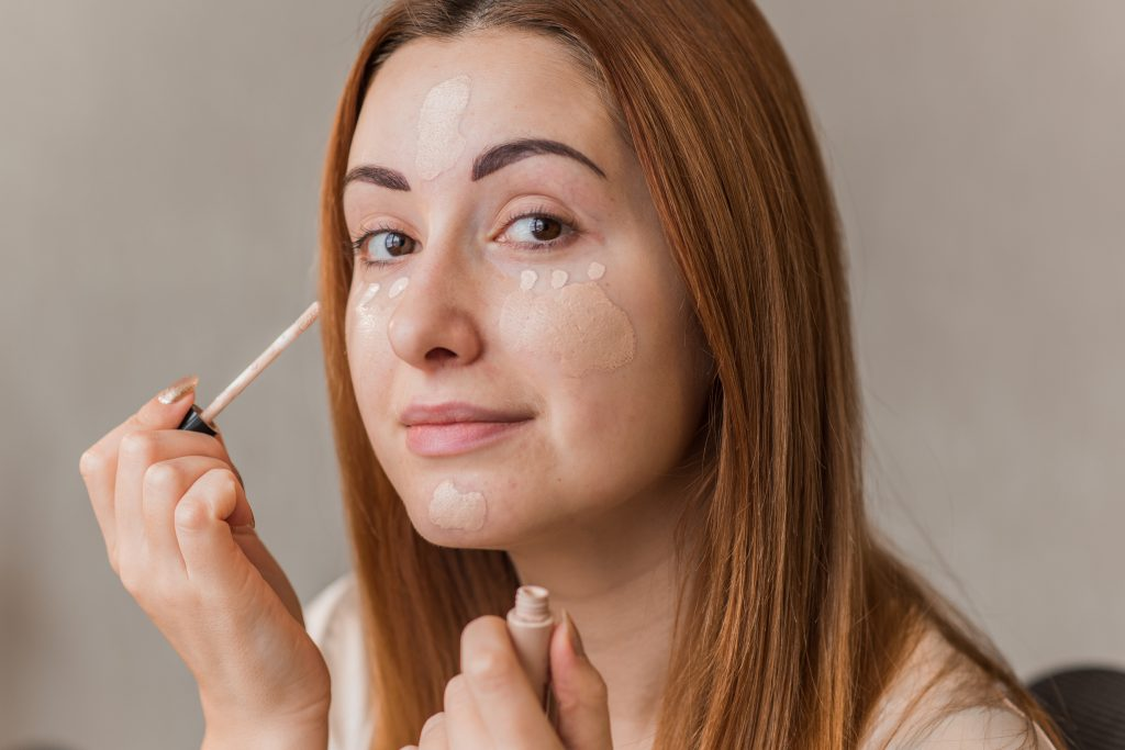 woman with auburn hair applying concealer to her face